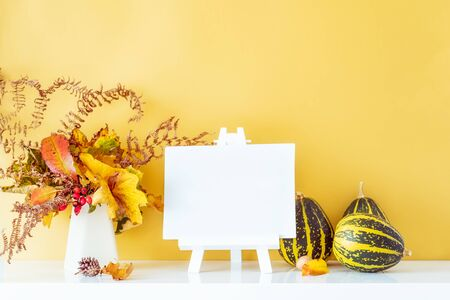 Empty blank canvas on a stand, decorative striped pumpkins, vase with bouquet of falling leaves and fern on golden wall background. Autumn natural home interior decor. Eco, simple style. Copy space Banco de Imagens