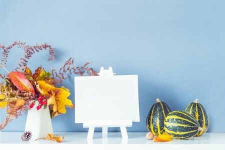 Empty blank canvas on a stand, decorative striped pumpkins, vase with bouquet of falling leaves and fern on blue wall background. Autumn natural home interior decor. Eco, simple style. Copy space