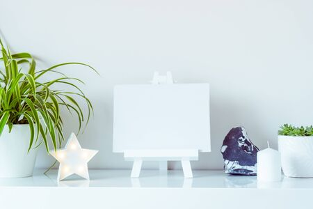 White scandinavian home interior design. Green plants in pots, star shape lamp, blank canvas on a stand, and stone detail on wall background. Minimalist simple hygge room decor. Close up. Copy space