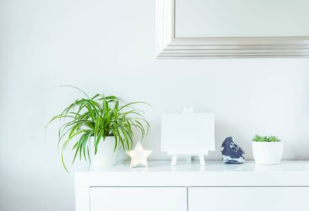 White scandinavian home interior design. Green plants in pots, star shape lamp, blank canvas on a stand, and stone detail on wall with mirror background. Minimalist simple hygge room decor. Copy space. Banco de Imagens