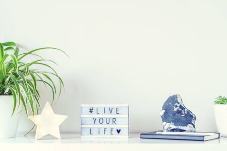 Workplace with star shape lamp, green plants, box with hashtag LIVE YOUR LIVE, notebook, stone decor on the white wall background. Light minimalism interior style. Motivation for work and achievements.