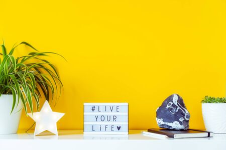 Bright workplace with star shape lamp, green plants, box with hashtag LIVE YOUR LIVE, notebook, stone decor on the yellow background. Simple minimalism interior style. Motivation for freelance work