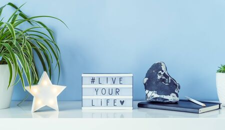 Workplace with star shape lamp, green plant, box with hashtag LIVE YOUR LIVE, notebook, stone decor on the blue background. Simple minimalism interior style. Motivation for freelance work. Wide banner.