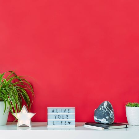 Bright workplace with star shape lamp, green plants, box with hashtag LIVE YOUR LIVE, notebook, stone decor on the red background. Minimalism interior style. Motivation for freelance work. Square card. Banco de Imagens