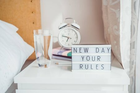 Good morning concept. Inspiration Motivational Life Quotes New day your rules message on lightened box with alarm clock, notebooks and glass of water on the bedside table in the sunlight. Copy space