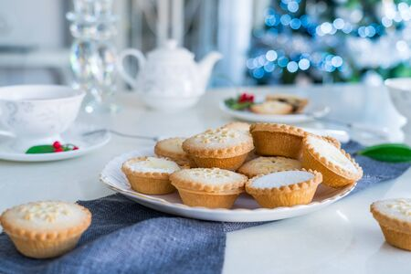 Traditional english festive pastry mince pies on served for tea time table with lighted christmas tree on background. Cozy home mood. Close up, selective focus. Copy space
