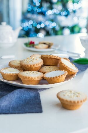 Traditional english festive pastry mince pies on served for tea time table with lighted christmas tree on background. Cozy home mood. Vertical card. Close up, selective focus. Copy space