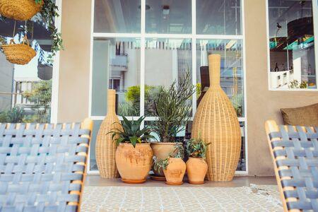Composition extérieure de grands vases en rotin et pots en céramique avec des plantes fraîches près de la fenêtre. Design extérieur éco naturel élégant. Décoration de maison. Espace de copie