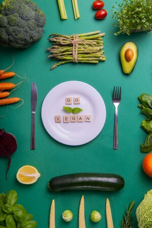 Top view set of healthy vegetables, white plate with Go vegan message on wooden blocks on green background. Vegetarian and vegan diet. Veganism. Sustainable lifestyle, plant-based foods. Vertical card.
