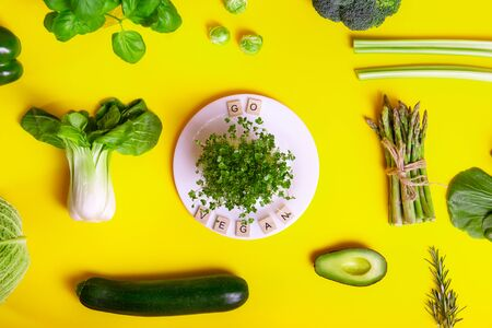Top view healthy raw vegetables on yellow background, white plate with sprouts and Go vegan message on wooden blocks. Vegetarian and vegan diet. Veganism. Sustainable lifestyle, plant-based foods
