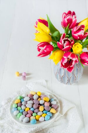 Festive Easter candies covered eggs in various pastel colors on the plate with vintage napkin near vase with fresh tulips on wooden table. Family holiday background. Light vertical card. Copy space