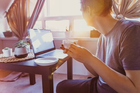 Young man working on laptop sitting near coffee table with cup of hot drink tea and enjoing sunset view. Workplace near window. Working at home. Back light, selective focus. Copy space. Slow living