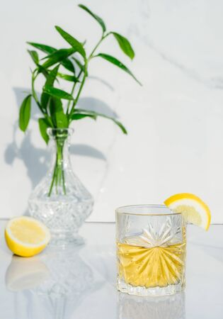 Crystal glass with yellow cocktail decorated with lemon. Vase with fresh greenery and glass goblet with green tea, alcohol drink on marble background. Direct sunlight and shadows. Minimalism. Vertical. 写真素材