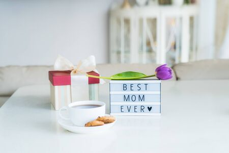 Mother's day background. Morning suprise - cup of tea with cookies, gift box, lightbox with words Best mom ever and tulip flower on it standing on the marble table with light interior view. Copy space. 写真素材