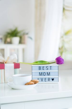 Mother's day background. Morning suprise - cup of tea with cookies, gift box, lightbox with words Best mom ever and tulip flower on the marble table with light interior view. Vertical card. Copy space.