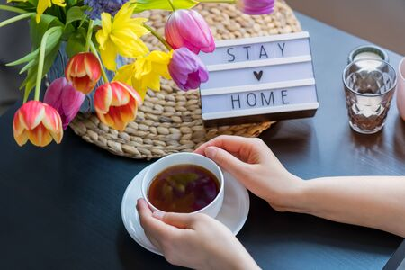 Female hands holding cup of hot tea drink sitting near coffee table with fresh spring tulips and daffodils flowers and lightbox with Stay home words. Quarantine concept. Selective focus. Copy space