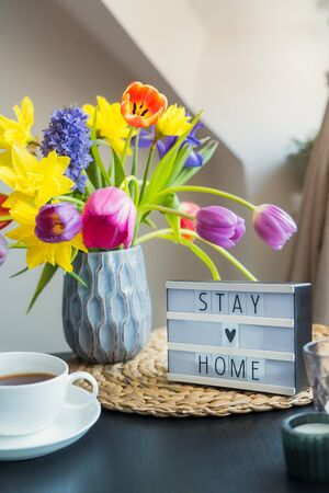 Cozy composition of cup of tea, lightbox with Stay home words and bouquet of fresh spring flowers on the coffee table near window. Everything for a calm stay at home. Selective focus. Vertical card