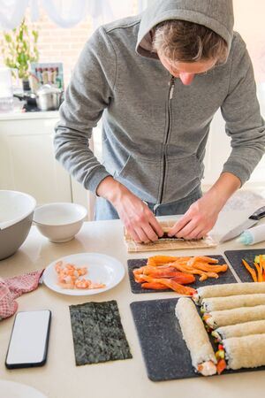 Young caucasian man making sushi at home following cooking online video classes on website via smartphone. Internet technology for modern lifestyle concept. Selective focus. Verticval card. Copy space.