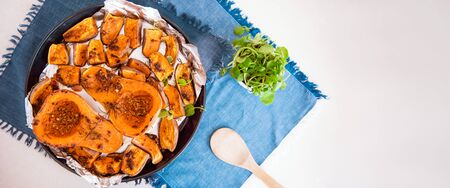 Top view baked roasted grilled whole orange pumpkin butternut squash and sweet potato with herbs on the baking sheet on blue napkin. Vegetarian and vegan food diet. Healthy eating concept. Wide banner. 写真素材