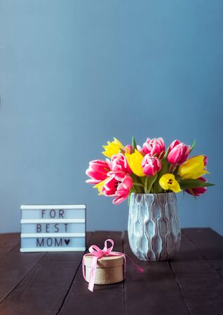 Pink and yellow tulip flowers in vase, craft gift box with satin ribbon and For best mom text stand on black wooden table and blue gray background. Festive vertical greeting card mockup. Copy space 写真素材