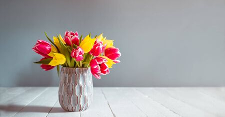 Fresh spring yellow and pink tulips bouquet in blue vase standing on black wooden table with gray background. Festive flowers for mother's or women's day. Mockup for greeting wide banner. Copy space