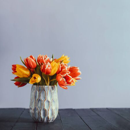 Fresh spring yellow and pink tulips bouquet in blue vase standing on black wooden table with gray background. Festive flowers for mother's or women's day. Mockup for greeting square card. Copy space