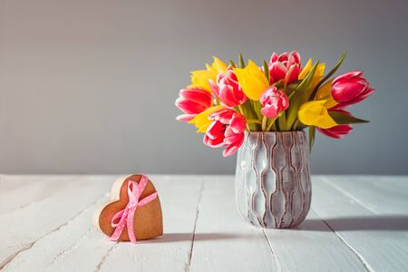 Bouquet of pink and yellow tulip flowers in a blue vase and heart shape gift box with satin ribbon bow on the white wooden table and grey background. Greetings for mother's or women's day. Card mockup.