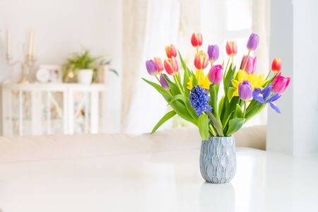 Fresh spring colorful bouquet of tulips, daffodils, irises in vase standing on white marble table with light classic design living room background. Festive flowers for gift. Mockup for greeting card