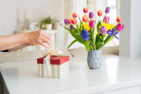 Close up woman opening gift box on marble table with colorful spring flowers bouquet in vase. Light classical interior room background. Happy birthday, woman's day, Mother's Day card. Copy space