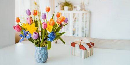 Fresh spring colorful bouquet of tulips, daffodils, irises in vase and gift box on white table with light classic design room background. Festive flowers for gift. Mockup for wide banner. Copy space.