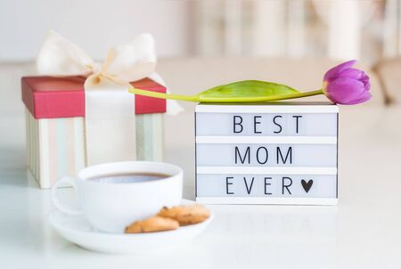 Mother's day background. Morning suprise - cup of tea with cookies, lightbox with words Best mom ever and tulip flower on it standing on the marble table with light interior view. Close up. Copy space.
