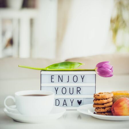 Good morning concept. Romantic breakfast - cup of hot drink, cookies, lightbox with message Enjoy your day and tulip flower on marble table with light interior view. Close up. Square card. Copy space Archivio Fotografico