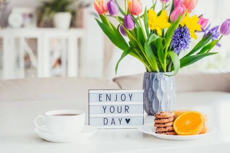 Good morning concept. Romantic breakfast - fresh spring flowers, cup of hot coffee drink, cookies, orange, lightbox with message Enjoy your day on marble table with light interior view. Copy space
