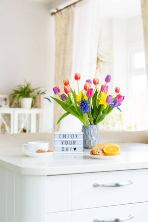 Good morning concept. Romantic breakfast - fresh flowers, cup of hot drink, cookies, orange, lightbox with message Enjoy your day on marble table with light interior view. Vertical card. Copy space