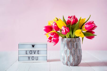 Lightbox with love you message and fresh spring yellow and pink tulips bouquet in a vase on white wooden table with pink background. Flowers as a gift for lover. Mockup for greeting card. Copy space 写真素材