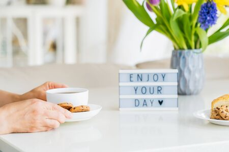 Good morning concept, breakfast time. Close up woman with cup of hot coffee drink, cookies, lightbox with message Enjoy your day and fresh flowers in vase on table with light interior view. Copy space.