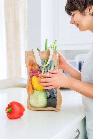 Woman holding reusable eco sackcloth fabric bag packaging with fresh organic vegetables on white kitchen table. Home delivery concept. Local farmer healthy food. Zero waste. Vertical card. Copy space 写真素材