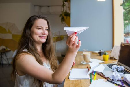 Focussed paper airplane in female hand. Blurred woman woman launches paper airplane sitting at her workplace with laptop, blanks for ideas, colorful stationery. Creative and Inspiration concept. Archivio Fotografico