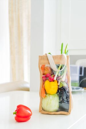 Fresh organic vegetables delivery concept. Reusable eco fabric bag packaging on marble white kitchen table. Local farmer healthy food. Zero-waste and plastic-free lifestyle. Vertical card. Copy space.