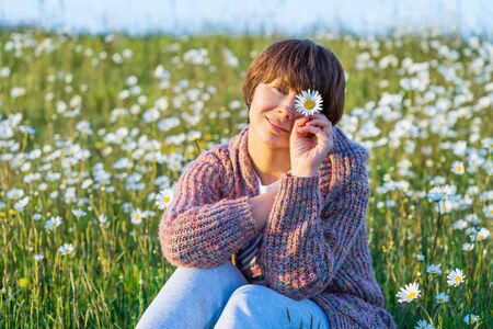 No makeup, a natural mixed-race woman is holding flowers in front of her eye while sitting in the camomile field at sunset gold hour. Warm sunny evening light. Natural beauty. Copy space. Foto de archivo