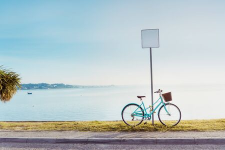 Vintage style bright bicycle parked near a blank road sign in the seafront quay. Sea view landscape with paving walking paths with a palm tree at sunset time. Calm and relax concept. Copy space Foto de archivo