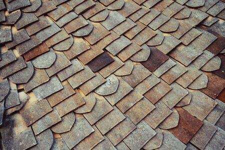 Close up roof tiles texture for background. Old Fashioned style Roof Tiles rows. English vintage ceramic tiles of various shapes Foto de archivo