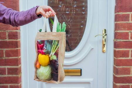 Fresh organic vegetable delivery concept. Female hand holding reusable eco fabric bag packaging in front of enter house door. Local farmer healthy food. Zero-waste, plastic-free lifestyle. Copy space.