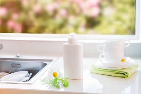 Eco friendly non-toxic cleaning dish soap with natural ingredients, chamomile flowers, clean white cups and plates near sink with dirty dish. Skincare for housekeeping. Bio organic cleaning supplies.