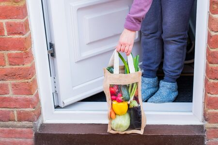 Fresh organic vegetable delivery concept. No face woman taking reusable eco fabric bag packaging in front of enter house door. Local farmer healthy food. Zero-waste, plastic-free lifestyle. Copy space