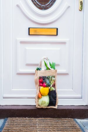 Fresh organic vegetable delivery concept. Reusable bio eco sackcloth fabric bag packagingstanding near entering house door. Local farmer healthy food. Zero-waste, plastic-free lifestyle. Copy space.