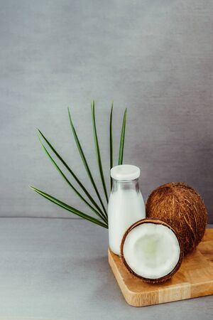 Fresh, healthy vegan plant base coconut milk with whole nuts and pulm leaf on gray background. Natural coconut oil for cooking and skincare. Selective focus. Vertical card. Copy space.