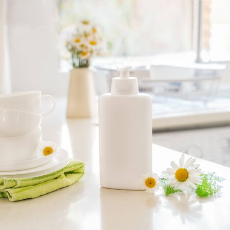 Eco friendly non-toxic cleaning dish soap with natural ingredients, chamomile flowers, clean white cups and plates on white kitchen table. Skincare for housekeeping. Bio organic cleaning supplies.