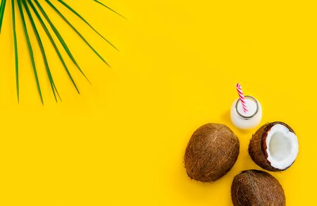 Top view coconut water drink, milk in a bottle with straw, and fresh coconuts with a green palm leaf on the yellow background. Summer exotic refreshment. Natural plant based food. Flatlay. Copy space. Archivio Fotografico