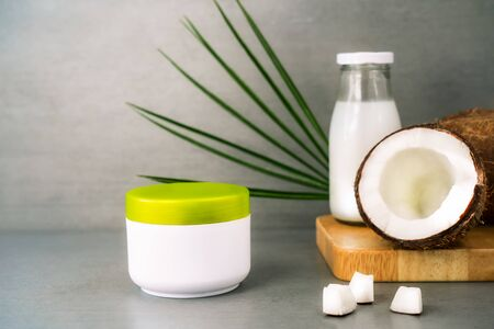 Spa cream for body skincare and hair with coconut oil, fresh coconuts, palm leaf and bottle with coconut butter on dark gray background. Natural cosmetics concept.Copy space.
